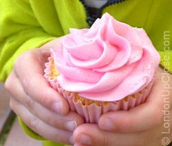 Little hands happily grasp a strawberry cheesecake cupcake at the Cabbages and Frocks Saturday Market, Marylebone