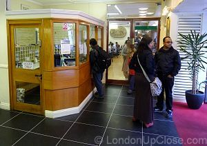 Buy your dinner ticket at the reception booth of the Indian YMCA in London, then go through the glass doors to the dining room.
