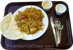 This dinner at the Indian YMCA in London consists of Chicken biryani, vegetable biryani, yoghurt raita and papadums, with cardamom pudding for dessert.