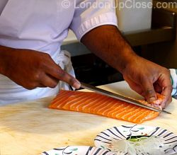 Preparing salmon for sashimi and sushi at Kulu Kulu Sushi. The chefs work in view of the diners, in the central preparation area.