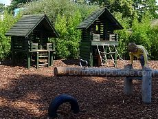 Playhouses and a seesaw at the Princess Diana Memorial Playground made out of a whole log.